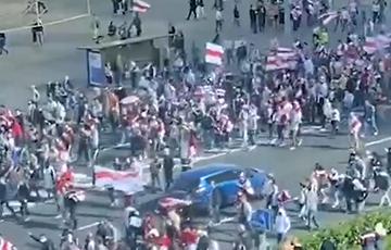Участники Марша Героев в Минске идут по проезжей части проспекта Победителей
