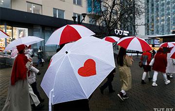 Девушки с бело-красно-белыми зонтами прошлись по проспекту Победителей